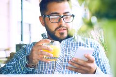 Handsome man with glasses drinking juice and looking at mobile phone in cafe. Handsome man with glasses and beard drinking juice and looking at mobile phone in stock image