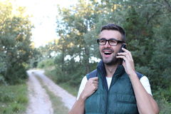 Handsome man with glasses phoning in the park. Beautiful man with hand on the face.  stock photography