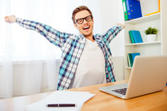 Handsome man in glasses stretching and yawning after long workin Royalty Free Stock Image