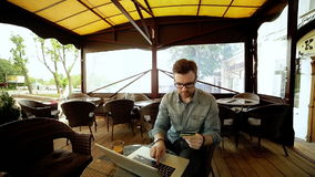 Handsome man in glasses using a laptop at cafe holding credit card in the hands. Handsome man in shirt and glasses using a laptop at cafe while holding credit stock footage