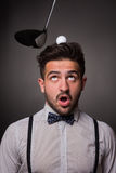 Handsome man with a golf ballon his head in studio. Portrait of handsome man with a golf ball on his head. Someone is going to kick the golf ball with brassie stock photo
