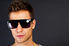 Handsome man in gray tank top with smile and sunglasses Royalty Free Stock Photo