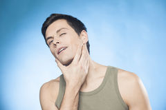 Handsome man in green tank top in front of mirror looking at his chin checking is he well-shaved Royalty Free Stock Images