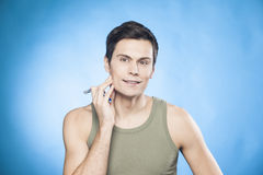 Handsome man in green tank top shaving.  Stock Photo