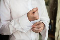 Handsome man groom buttoning elegant stylish white shirt while p Stock Photos