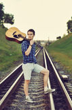 Handsome man with guitar in hand. Outdoors Stock Photography