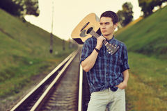 Handsome man with guitar in hand. Outdoors Royalty Free Stock Photos