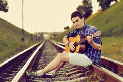 Handsome man with guitar on railway road Stock Photos