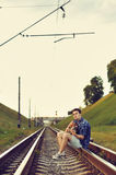 Handsome man with guitar on railway road Stock Image