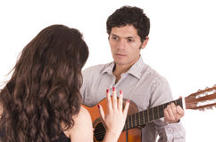 Handsome man with guitar serenading young girl Royalty Free Stock Photo