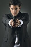 Handsome man with a gun. Handsome man with elegant dress hold a gun with two hands royalty free stock images