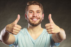 Handsome man guy giving thumb up gesture. Portrait of happy smiling handsome man guy giving thumb up gesture in studio on black. Success Stock Photography