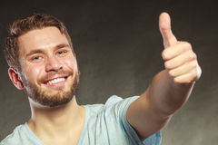 Handsome man guy giving thumb up gesture. Portrait of happy smiling handsome man guy giving thumb up gesture in studio on black. Success Stock Images