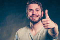 Handsome man guy giving thumb up gesture. Portrait of happy smiling handsome man guy giving thumb up gesture in studio on black. Success. Instagram filter Stock Photo