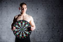 Handsome man in the gym holding a dartboard target. The concept of success and achievement of goals, results Royalty Free Stock Images