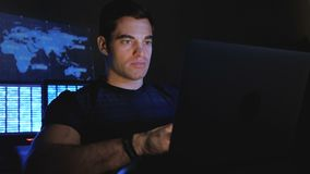 Handsome male hacker programmer works at a computer at night in a data center filled with monitor screens. Handsome man hacker programmer works at a computer at stock video