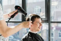 Handsome man at the hairdresser getting a new haircut stock photo