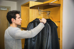 Handsome Man Hanging his Coats Inside his Wardrobe Royalty Free Stock Images