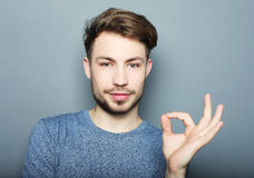 Handsome man happy smile, hold hand with ok gesture sign Royalty Free Stock Image