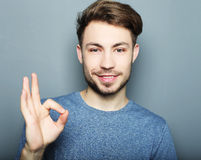 Handsome man happy smile, hold hand with ok gesture sign Stock Image