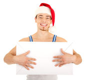 Handsome man has a present for you. Young handsome smiling man in red Christmas hat with big white carton box. Isolated on white background. Focus on eyes Royalty Free Stock Photo