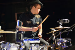 Handsome man in hat and black shirt plays drum set Royalty Free Stock Photos