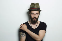 Handsome man in hat.Brutal bearded boy with tattoo Stock Image
