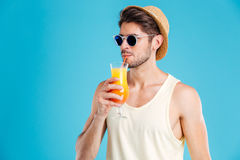 Handsome man in hat and sunglasses drinking fresh orange juice Stock Photography