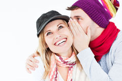 Handsome man with hat telling secret to girlfriend. Handsome man with hat telling a secret to his laughing girlfriend against a white background stock images
