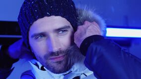 Handsome man in hat and winter jacket at snowfall closeup