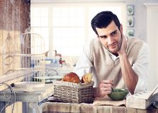 Handsome man having breakfast in cottage interior Stock Images