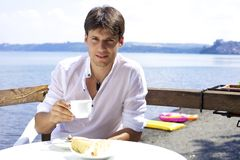 Handsome man having breakfast in front of lake Stock Photos