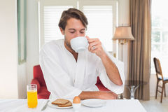 Handsome man having breakfast in his bathrobe drinking coffee Stock Photo