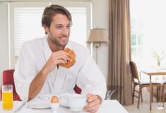 Handsome man having breakfast in his bathrobe. At home in the living room royalty free stock images