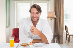 Handsome man having breakfast in his bathrobe smiling at camera Royalty Free Stock Image