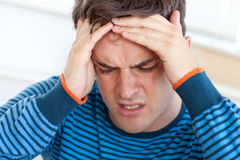 Handsome man having a headache in the living-room Royalty Free Stock Photography