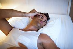 Handsome man having a headache lying on the white bed. Bedroom b. Ackground. View from above Royalty Free Stock Photos