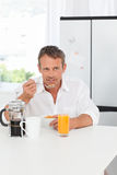 Handsome man having his breakfast in the kitchen Stock Images