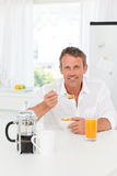 Handsome man having his breakfast in the kitchen Royalty Free Stock Images