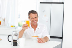 Handsome man having his breakfast in the kitchen Stock Photography