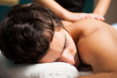 Handsome man having a massage Stock Photos