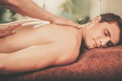 Handsome man having massage in spa salon Stock Images