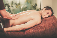 Handsome man having massage in spa salon Stock Photos