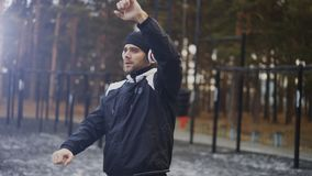 Handsome man in headphones doing stretching exercise while listening music in winter park. Outdoors Stock Photo