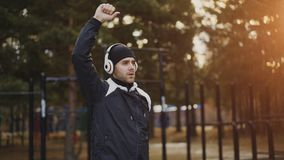Handsome man in headphones doing stretching exercise while listening music in winter park. Outdoors Royalty Free Stock Image