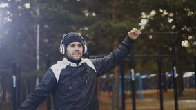 Handsome man in headphones doing stretching exercise while listening music in winter park. Outdoors Stock Photos