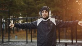 Handsome man in headphones doing warm-up exercise while listening music in winter park. Outdoors Royalty Free Stock Photo