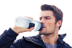 Handsome man in headphones drinking water Royalty Free Stock Images