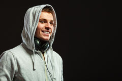 Handsome man with headphones listening to music. Smiling handsome hooded man with headphones listening to music sideview dark background Royalty Free Stock Photography