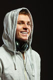 Handsome man with headphones listening to music. Smiling handsome hooded man with headphones listening to music sideview dark background Royalty Free Stock Photos